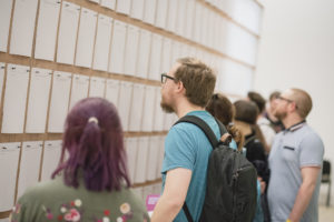 Photo of people looking at paper on wall